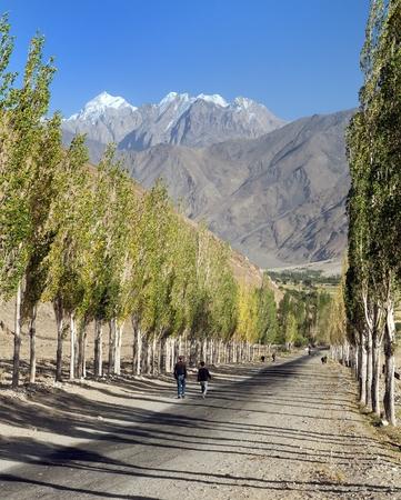 Carretera de Pamir, camino y callejón de álamos y montañas de Pamir, corredor y valle de Wakhan, región de Gorno-Badakhshan, frontera de Tayikistán y Afganistán, techo del mundo Foto de archivo