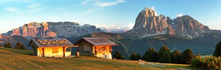 Evening panoramic view of two small cabin, Sella Gruppe or Gruppo di Sella and Langkofel, South Tirol, Italian dolomites mountains, Italy