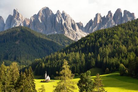 view of Geislergruppe or Gruppo dele Odle with chapel or small church, Italian Dolomites Alps mountains