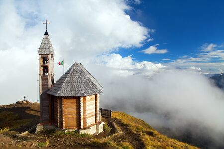 Small wooden church or chapel on the mountain top Col di Lana and cloudy sky, Alps Dolomites mountains, Italy