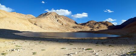 Pamir mountains near Pamir highway, evening view of small lake and mounts mirroring in lake, Tajikistan Stock Photo