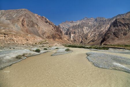 Tributary of Panj river and Pamir mountains. Panj is upper part of Amu Darya river. Panoramic view.Tajikistan and Afghanistan border