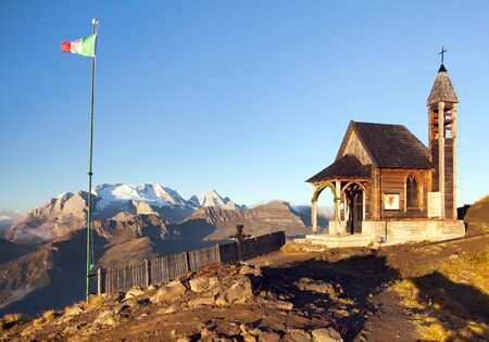 Small wooden church or chapel on the mountain top Col di Lana and Mount Marmolada, Alps Dolomites mountains, Italy 版權商用圖片