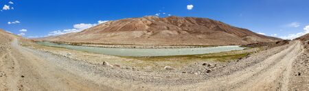 Panoramic view of Pamir river and pamirs unpaved road, Pamir mountains on Tajikistan and Afghanistan border Gorno-badakhshan region