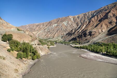 Pamir highway M41 international road or pamirskij trakt. Panj river and Pamir mountains. Panj is upper part of Amu Darya river. Panoramic view.Tajikistan and Afghanistan border, Gorno-badakhshan region