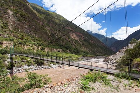 rope hanging suspension bridge and Rio Apurimac, Apurimac is upper part of the longist and the largest Amazon river, view from Choquequirao trekking trail, Cuzco area, Peruvian Andes