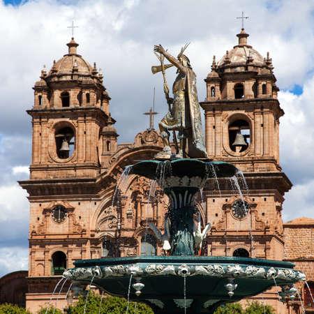 Statue of Inca Pachacutec on fountain and catholic church on Plaza de Armas, Cusco or Cuzco town, Peru