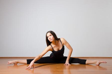 ballet: Hermosa bailarina de ballet realizar dividida en el suelo.