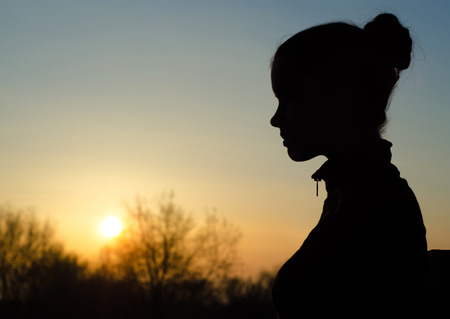 profile silhouette: Silhouette of the beautiful girl in the nature at summer sunset. Stock Photo
