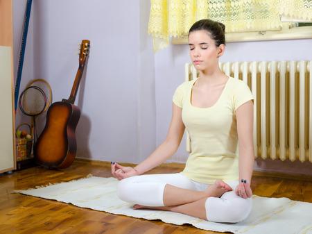 teenage girl: Beautiful teenage girl meditating in yoga pose in her room.