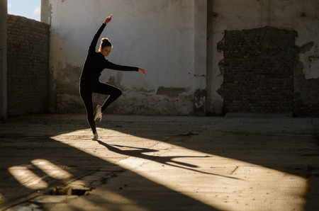 Young modern dancer exercising and dancing in abandoned building. Stock Photo