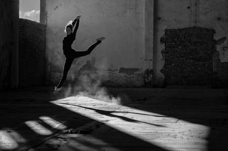 Beautiful young ballerina dancing in abandoned building.