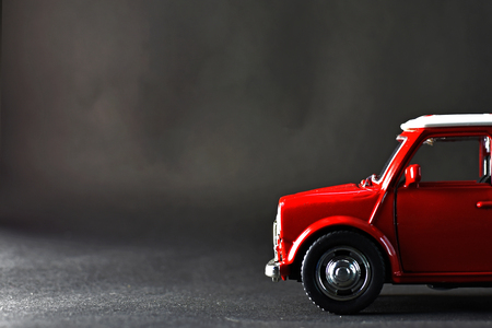 A small red car on a tinted floor is almost black Stock Photo