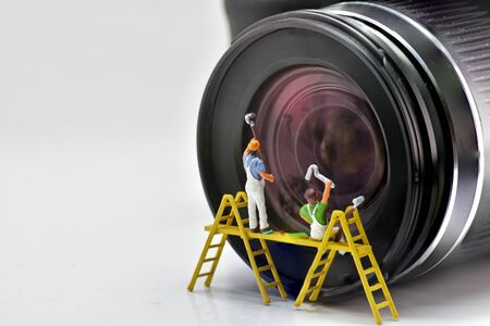 Minifigure Concept, cleaner Cleaning the lens of the camera. Reklamní fotografie