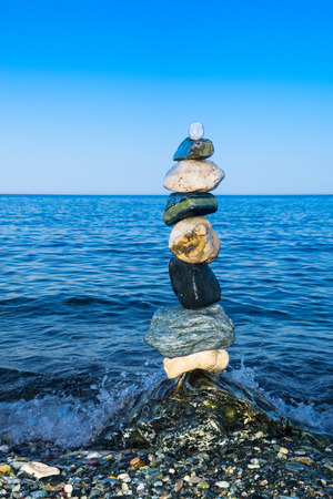 deliberation: Colorful zen balancing rocks with blue sea background
