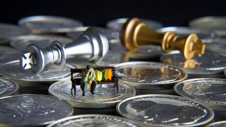 Silver chessboard, silver and gold chess, silver coins with black background, homeless sitting on the bank Stock Photo