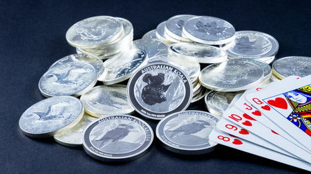 Playing cards and silver coins with black background