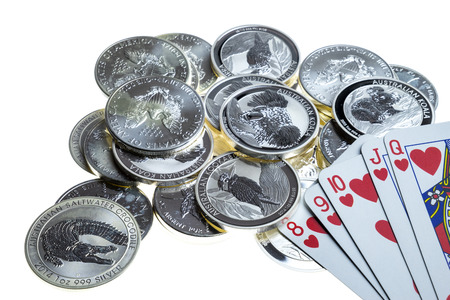 White table with silver coins, silver money table with silver coins, money and playing cards