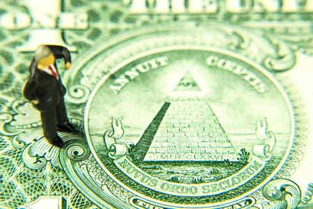 Dollar banknote detail, manager figurine, novus ordo seclorum