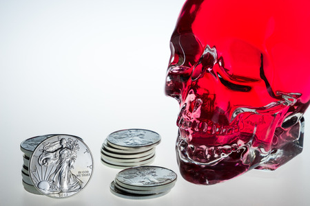 Investor, red crystal skull, glass brainpan with silver coins and white background Stock Photo