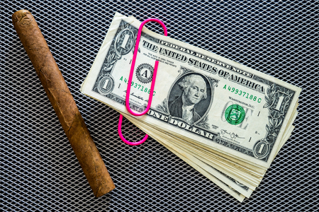 stapled: Cuban cigar and dollars with pink clip