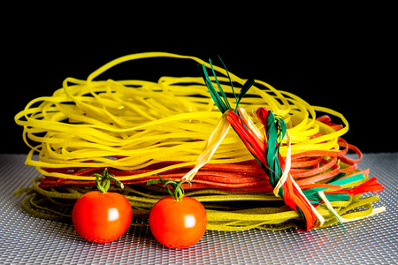 wire: Tasty color pasta with two red tomatoes and grid background Stock Photo