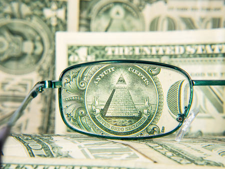 new world order: Glasses focused on dollar banknote, dollar money with pyramid and eye, detail