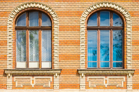 Historical building facade, detail, two windows and bricks wall building exterior