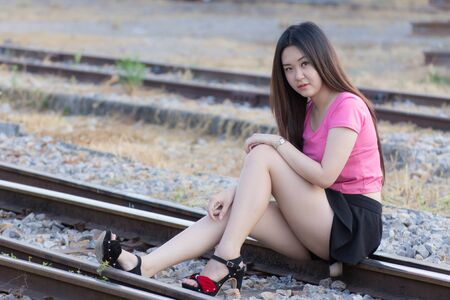 Portrait of a beautiful Thai woman smiling on train station platform photo