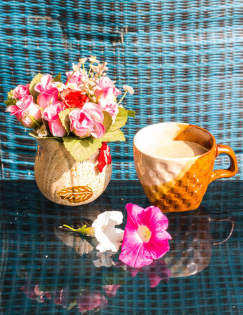 Still Life , Coffee Cup  White  Rose Plastic And Petunia flowers photo