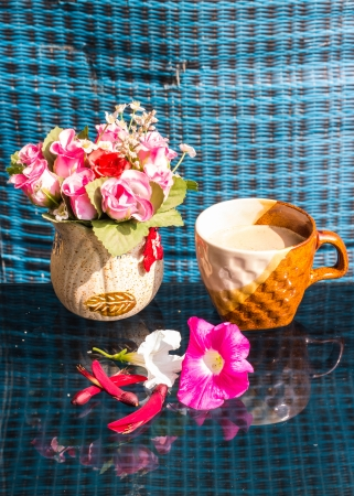 Still Life , Coffee Cup  With  Rose Plastic, Erythrina variegata And Petunia flowers photo