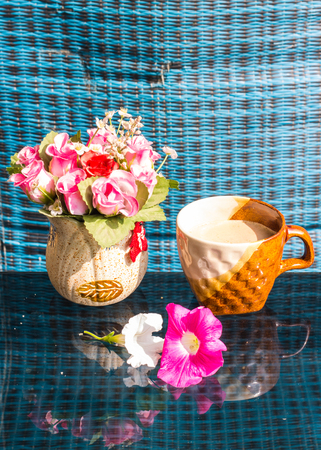 Still Life , Coffee Cup  With  Rose Plastic And Petunia flowers photo