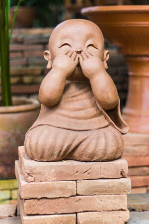smiling buddhist novice made of clay, Thai style photo