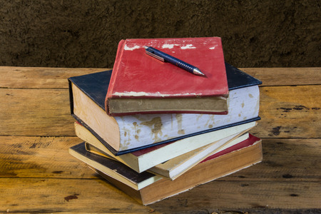Vintage pencil and old books on wooden deck table with soil wall photo