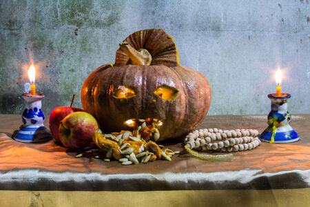 Halloween still life with pumpkins, apple, candles and rosary photo