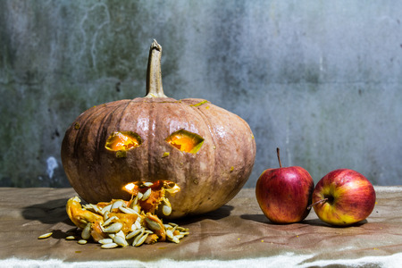 Haunted carved pumpkins for Halloween with apple photo
