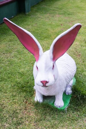 sweet grass: white rabbit statue in lawn Stock Photo