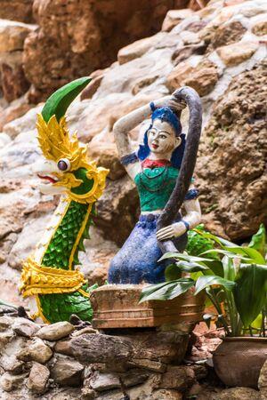 isaan: Phra Mae Thorani with naga statue, Thai angel statue Stock Photo