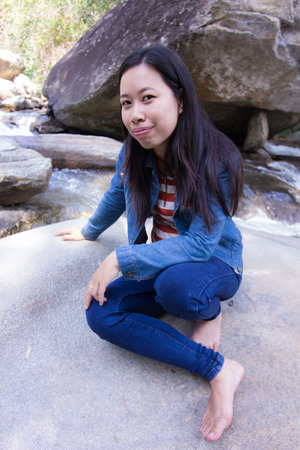 boater: Thai woman with rock in river