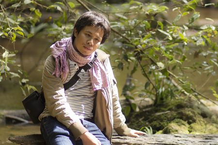 vacant asia man sitting Timber in river forest
