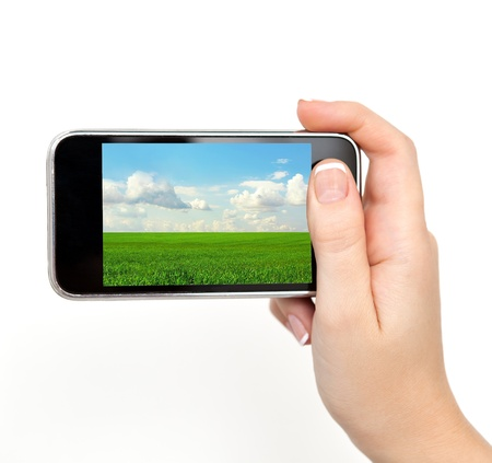 isolated woman hand holding the phone with the image of green grass and blue sky field photo