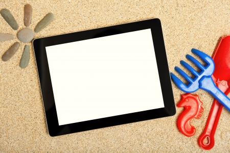 Tablet in the sand for children toys Stock Photo - 17205411