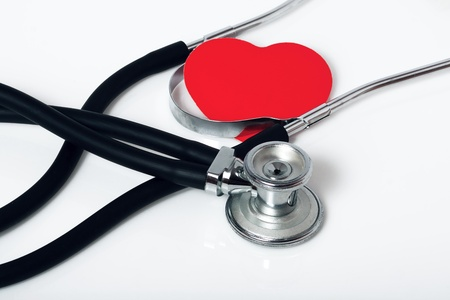 Medical stethoscope and a red heart on a white background photo