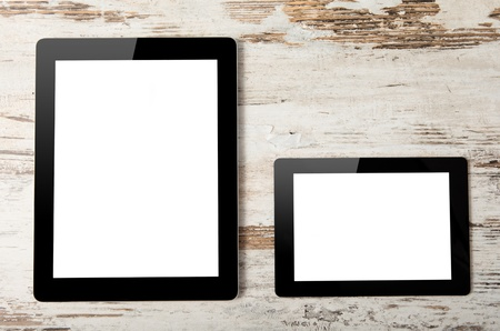 tablet computer and mini tablet with isolated screen on a background of wood photo