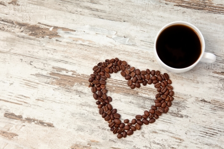 coffee beans in the form of heart and a cup of coffee on a wooden table photo