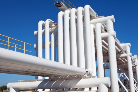 gas supply: Industrial pipe with gas and oil and water on a background of blue sky