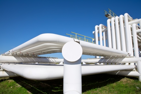 gas plant: Industrial pipe with gas and oil and water on a background of blue sky
