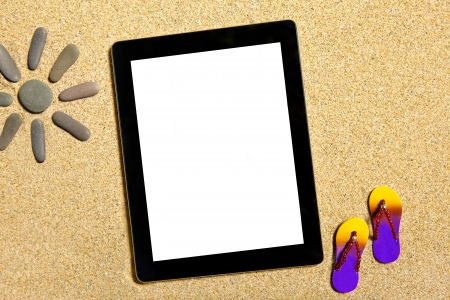Isolated tablet lying on the sand photo