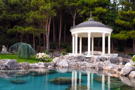 gazebo by the pond in a beautiful green park Stock Photo