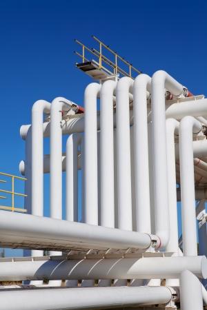 turbina de vapor: Tubería industrial con gas y el petróleo y el agua sobre un fondo de cielo azul